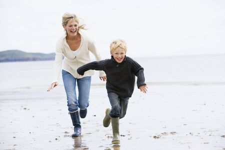 Mother and son running on beach smiling photo