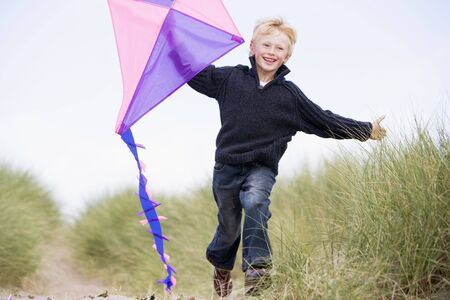 winter escape: Young boy running on beach with kite smiling Stock Photo
