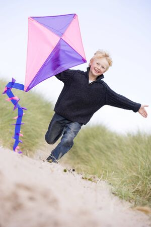 flying a kite: Young boy running on beach with kite smiling Stock Photo