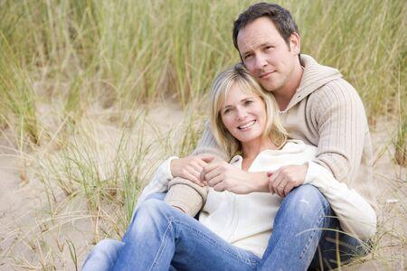 winter couple: Couple sitting on beach smiling Stock Photo