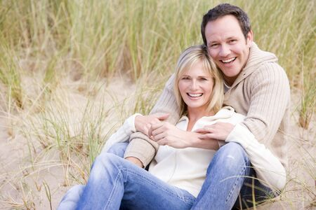 30s: Couple sitting on beach smiling Stock Photo