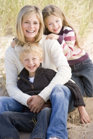 Mother and two young children sitting on beach smiling photo