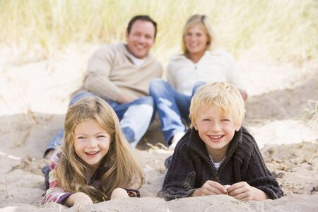 Family relaxing on beach smiling photo