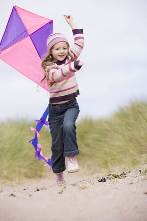 winter escape: Young girl on beach with kite smiling Stock Photo