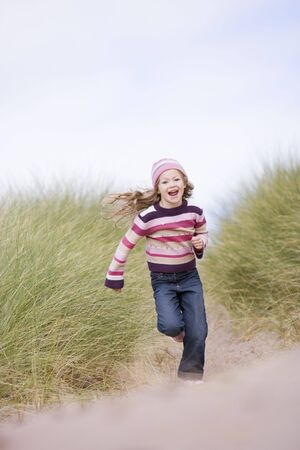 winter escape: Young girl running on beach smiling Stock Photo