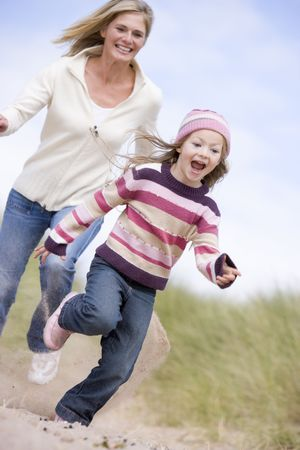 winter escape: Mother and daughter running on beach smiling