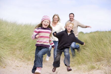 Family running on beach smiling photo