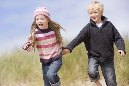 winter escape: Two young children running on beach holding hands smiling