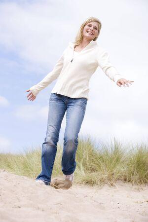 winter escape: Woman walking on beach smiling Stock Photo
