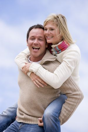 piggyback: man giving woman piggyback ride outdoors smiling