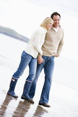 parejas caminando: Pareja caminar en la playa tomados de la mano sonriendo