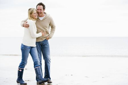 Couple walking on beach arm in arm smiling Stock Photo - 3599737