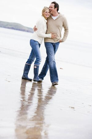 strolling: Couple walking on beach arm in arm smiling