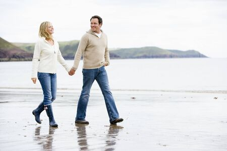 Couple walking on beach holding hands smiling photo