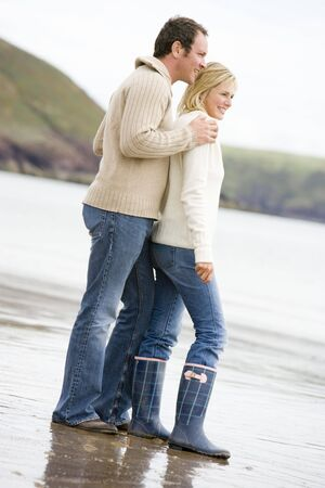 Couple standing on beach smiling photo