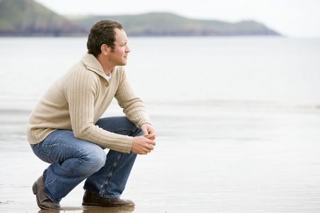 middle aged men: Man crouching on beach
