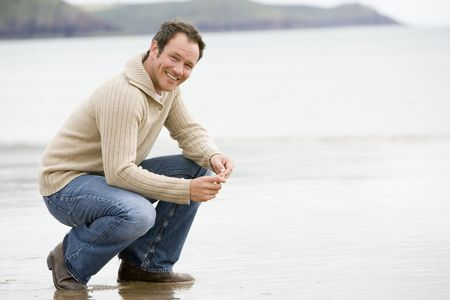 offset view: Man crouching on beach smiling