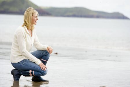 crouching: Woman crouching on beach smiling