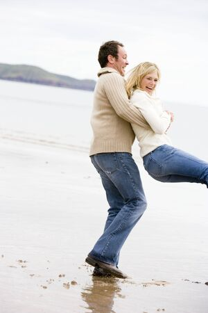 Couple playing on beach smiling photo