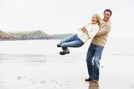 adult couple: Couple playing on beach smiling