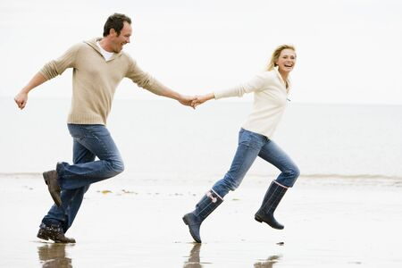 mujeres corriendo: Pareja corriendo en la playa tomados de la mano sonriendo
