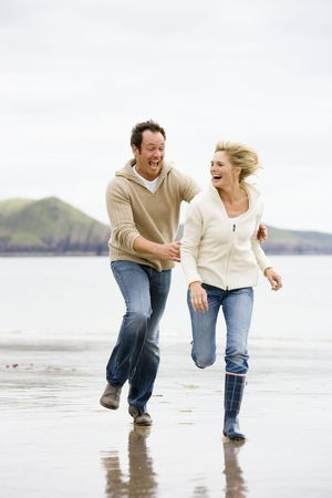 Couple running on beach smiling Stock Photo - 3599682