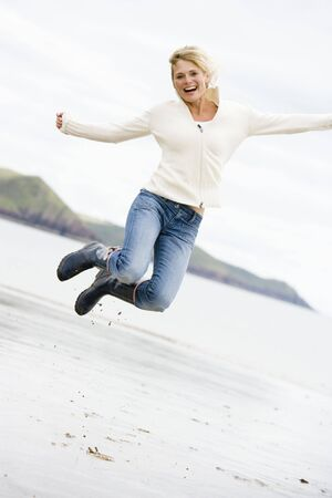offset view: Woman jumping on beach smiling Stock Photo
