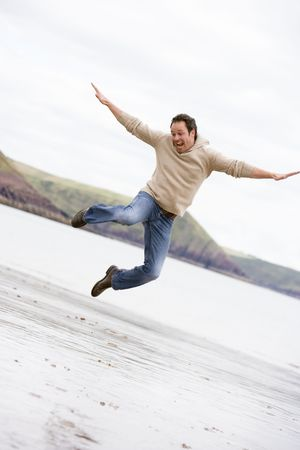Man jumping on beach smiling Stock Photo - 3599668