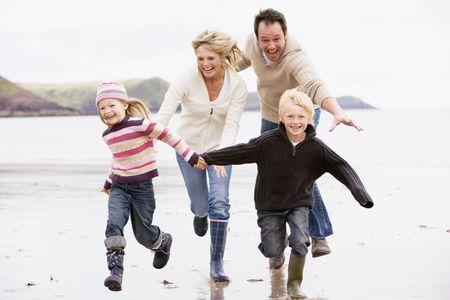 hermanos jugando: Familia ejecuta en la playa tomados de la mano sonriendo  Foto de archivo