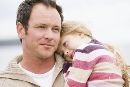 Father holding daughter at beach photo
