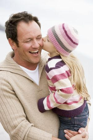 Father holding daughter kissing him at beach smiling photo