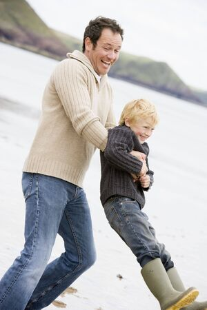 Father holding son at beach smiling photo