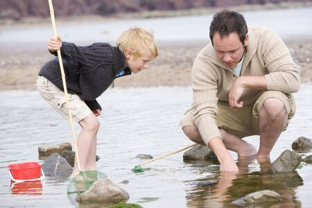 discovering: Father and son at beach fishing Stock Photo