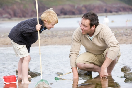 winter escape: Father and son at beach fishing Stock Photo