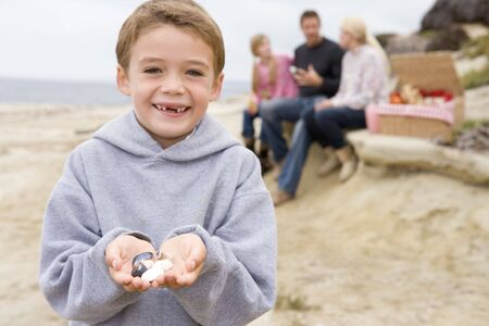 Family at beach with picnic smiling focus on boy with seashells photo