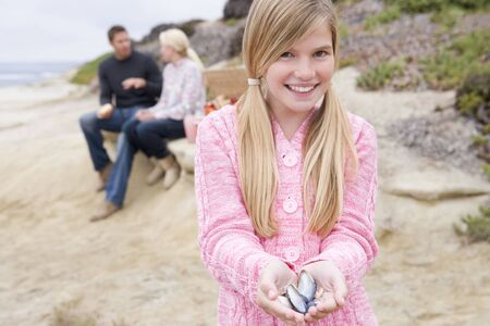 Family at beach with picnic smiling focus on girl with seashells photo