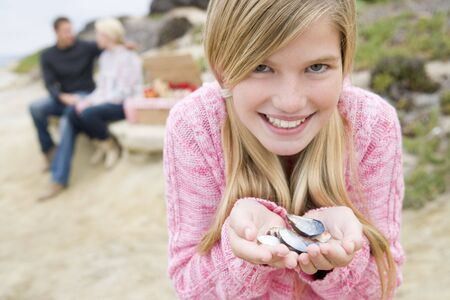 at beach with picnic smiling focus on girl with seashells photo
