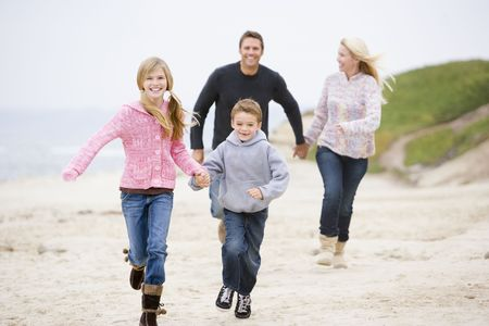 Family running at beach holding hands smiling photo