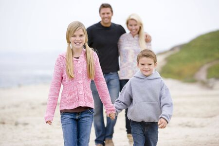 Family walking at beach holding hands smiling Stock Photo - 3476633