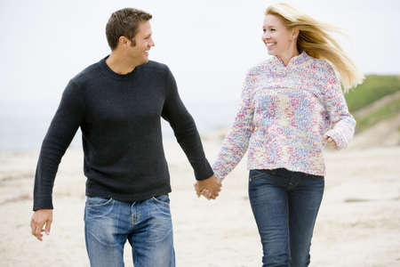 Couple walking at beach holding hands smiling Stock Photo - 3476795
