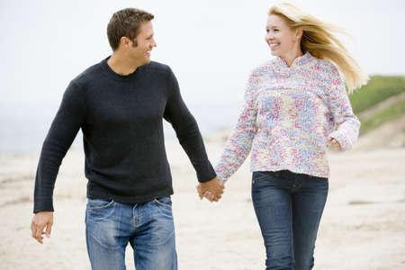 dos personas hablando: Pareja a pie de playa en la mano sonriente