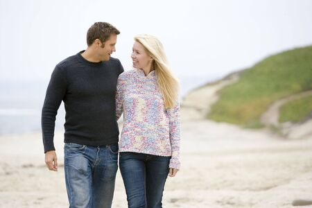 40s: Couple walking at beach smiling