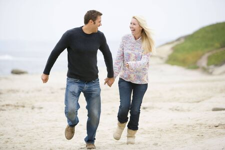 Couple running at beach holding hands smiling photo