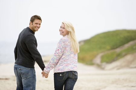 Couple walking at beach holding hands smiling photo