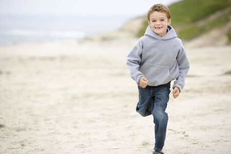 comfy: Young boy running on beach smiling