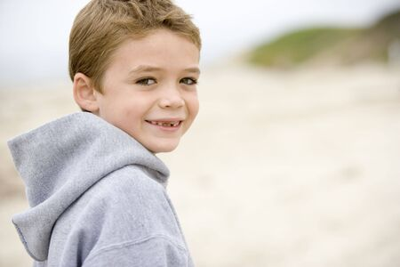 young boy smiling: Young boy standing on beach smiling Stock Photo