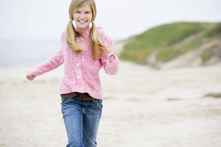 Young girl running at beach smiling photo