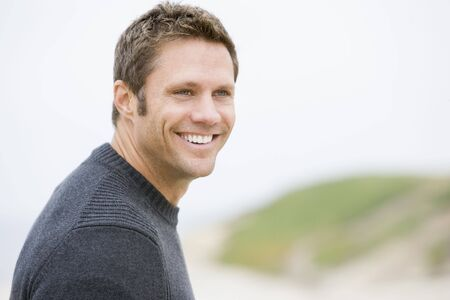 Man standing at beach smiling photo
