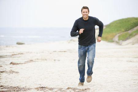 offset view: Man running at beach smiling Stock Photo
