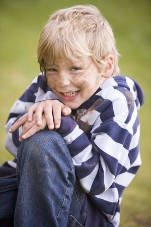 Young boy sitting outdoors dirty and smiling Stock Photo - 3476852